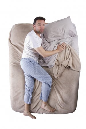 Photo for Top view of sleep deprived man on a bed - Royalty Free Image