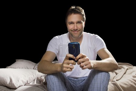 Man in bedroom using cell phone