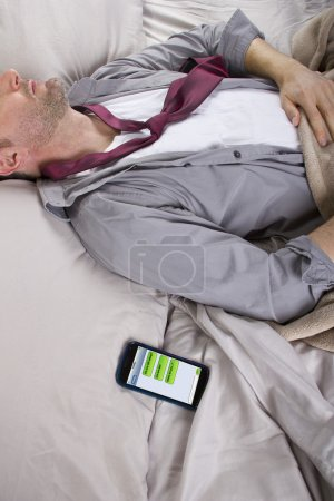 Man sleeping and receiving text messages from work