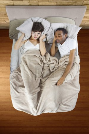 Unable to sleep in bed because of snoring partner