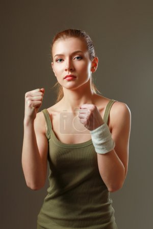 sporty muscular woman , isolated against grey background