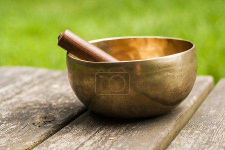 Photo for Golden singing bowl on a wood table - Royalty Free Image