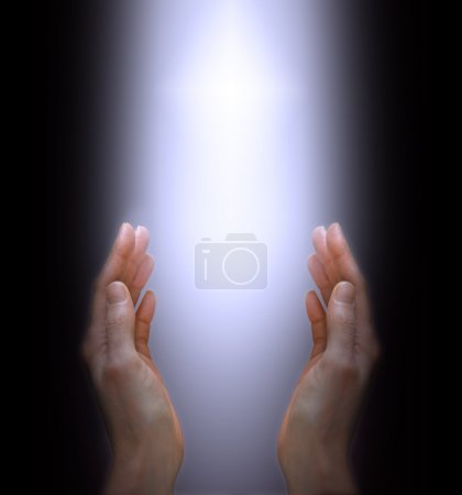 Photo for Female outstretched hands and bright shaft of light on a black background - Royalty Free Image