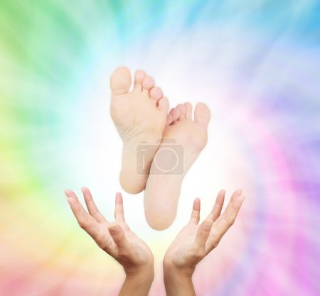 Photo for Reflexologist outstretched hands with feet floating above on a spiraling healing reflexology energy background - Royalty Free Image