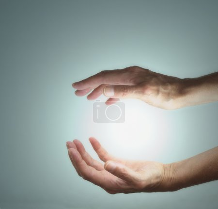 Photo for Female healer's hands with ball of energy between on a light blue grey background - Royalty Free Image