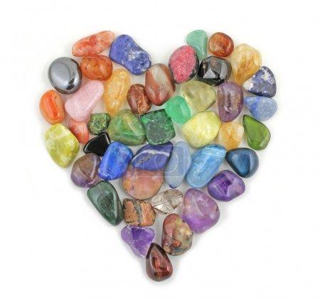 Photo pour Un cœur d'amour formé de pierres précieuses tombées sur un fond blanc - image libre de droit