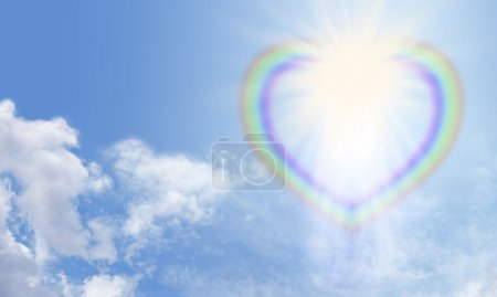 Photo for Wide blue sky with fluffy clouds and heart shaped rainbow bursting with light star formation on right side - Royalty Free Image