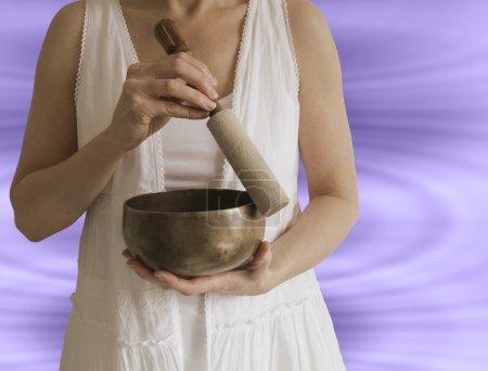 Photo pour Femelle guérisseur sonore à l'aide de bol chantant tibétain avec effet d'onde sonore en arrière-plan - image libre de droit