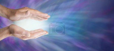 Photo pour Homme avec les mains tendues avec une boule de lumière entre sur un fond d'énergie bleue - image libre de droit