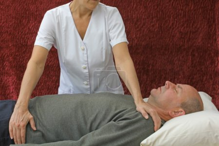 Photo pour Client mâle couché sur le canapé avec guérisseur thérapeute de polarité féminine channeling de guérison - image libre de droit