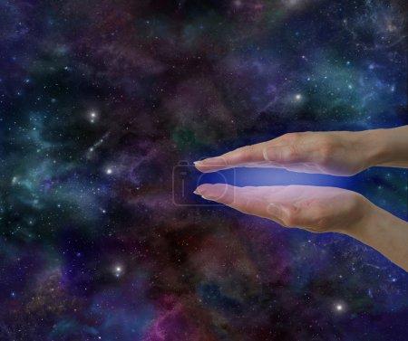 Photo pour Les mains parallèles du guérisseur montrant une aura électromagnétique bleue sur un fond d'espace profond avec beaucoup d'espace de copie - image libre de droit