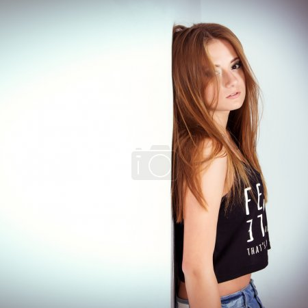 Beautiful young woman in denim shorts is in the Studio on the white-blue background