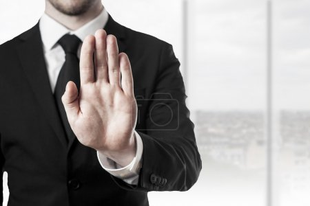 Photo pour Homme d'affaires en costume noir, tenant la main arrêt dans salle de bureau - image libre de droit