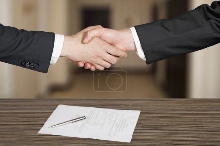 Business handshaking in office