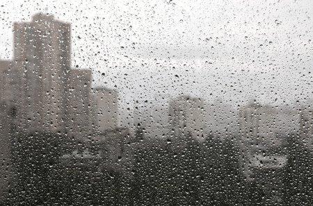 Photo pour La pluie tombe sur un fond de verre. Vue paysage urbain jeter fenêtre humide . - image libre de droit