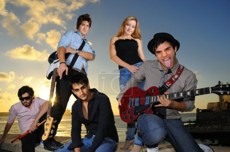 Photo for Portrait of young musical band posing outdoors at sunset with instruments - Royalty Free Image