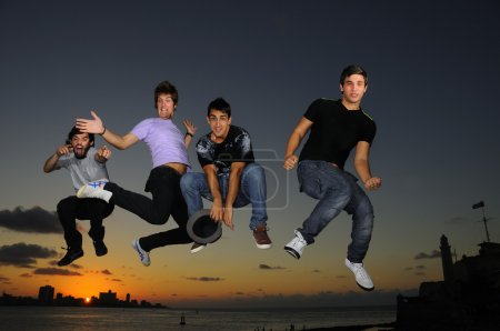 Happy young male group jumping  at sunset