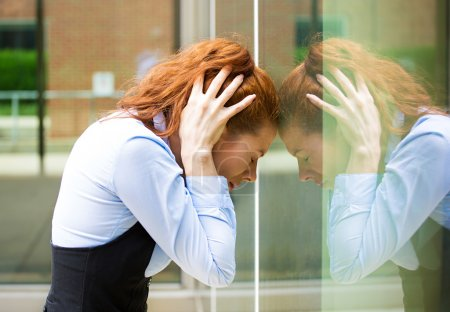 Photo for Closeup portrait unhappy sad young business woman head on window bothered by mistake having bad headache isolated background corporate office. Negative human emotion facial expression feeling reaction - Royalty Free Image