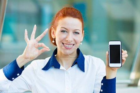 Happy woman showing her smart phone giving ok sign
