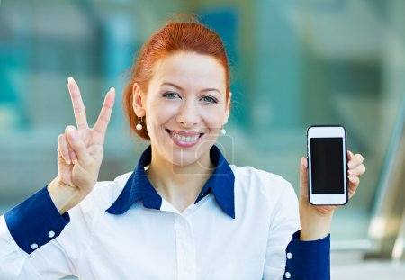 Happy woman showing her smart phone giving victory sign