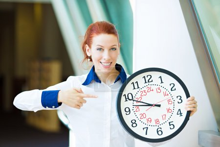 Business woman pointing on wall clock