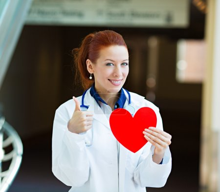 Doctor holding heart giving thumbs up