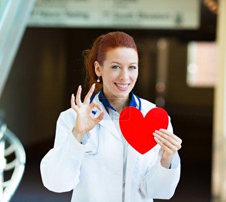 Photo pour Portrait rapproché femme souriante heureuse professionnelle de la santé, femme médecin de famille, cardiologue avec stéthoscope tenant coeur rouge, donnant ok signe isolé fond couloir de l'hôpital. Plan patient - image libre de droit