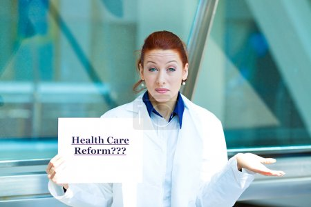 Confused doctor holding health care reform???sign
