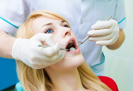 Dentist examining young adult patient, doing cleaning of teeth