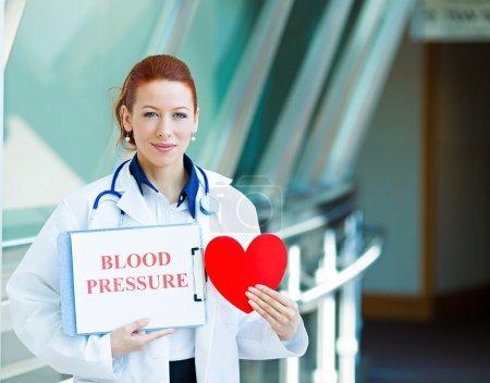 Photo pour Closeup portrait heureux souriant femelle de santé professionnelle, femme médecin de famille, cardiologue avec stéthoscope tenant coeur, tension artérielle signe isolé fond de couloir de l'hôpital. plan de patients - image libre de droit