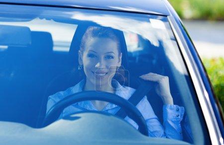Woman pulling on seatbelt inside black car