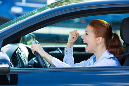 Photo pour Closeup portrait mécontent femme agressif au volant de voiture, criant à quelqu'un, main poing vers le haut dans l'air en colère en colère isolé fond de trafic. concept d'intelligence émotionnelle. émotion humaine négative - image libre de droit