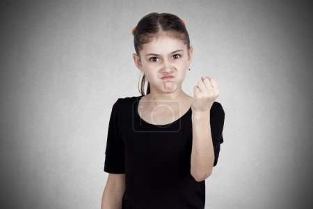 Angry little girl showing fist to someone