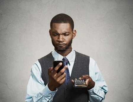 Corporate executive holding mobile phone and calculator