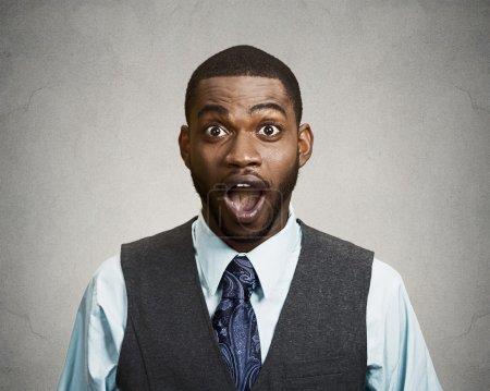 Foto de Closeup retrato feliz joven, boca abierta mirando impactado, sorprendido en fondo gris negro completa incredulidad aislado. emociones positivas, expresiones faciales, sentimiento, actitud, reacción - Imagen libre de derechos