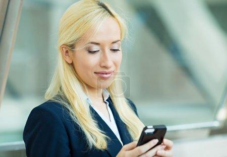 Photo pour Closeup portrait, heureuse, blonde fille, sourire, regardant la compagnie cellulaire, isolé siège de fond. expression faciale, réaction. femme d'affaires envoyer SMS depuis son portable. - image libre de droit