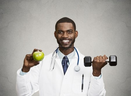 Happy doctor holding green apple, dumbbell