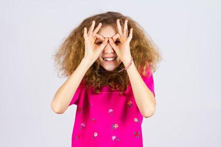 Photo pour Gros plan portrait jeune fille assez heureuse et drôle regardant à travers ses doigts comme des jumelles, cherchant quelque chose, regardant vers l'avenir à la caméra, fond gris isolé. Symbole du signe positif - image libre de droit