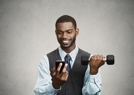 Happy executive reading good news on smart phone, lifting weight