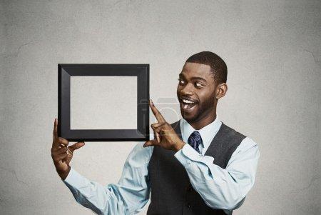 Photo pour Gros plan portrait heureux souriant confiant beau homme d'affaires de l'entreprise, dirigeant d'entreprise tenant vide cadre photo noire avec espace de copie. Expressions faciales positives, émotions, attitude, réaction - image libre de droit