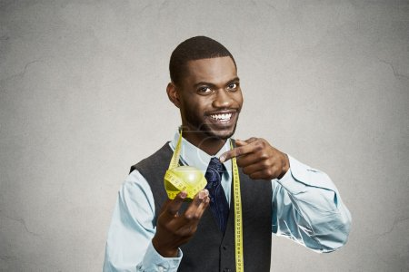 Happy executive advising on healthy diet, holding green apple