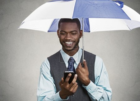 Happy executive reading good news on a smart phone, holding umbr