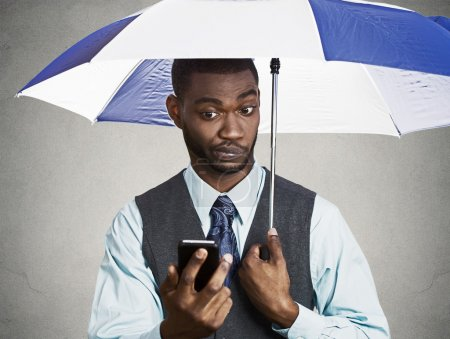 Executive man holding smart phone, reading news on a rainy day