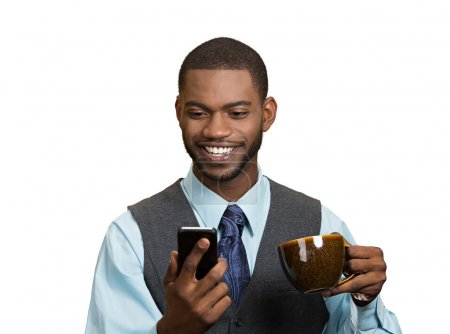 Smiling businessman reading news on mobile and drinking tea