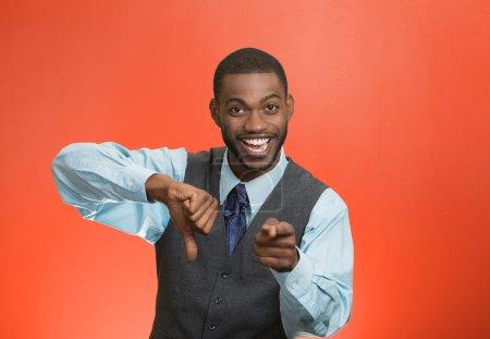 Photo pour Gros plan portrait sarcastique jeune homme montrant un pouce vers le bas signe geste de la main, heureux que quelqu'un a fait erreur, perdu, échoué isolé fond rouge. Émotions négatives, expressions faciales, sentiments - image libre de droit