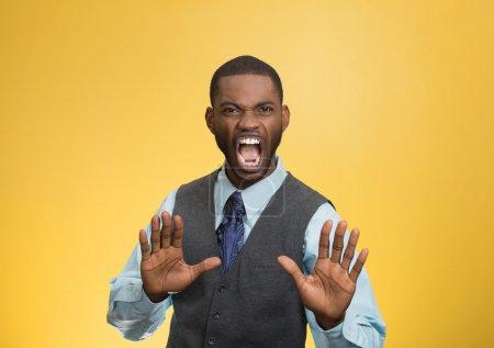 Photo pour Gros portrait furieux furieux énervé mécontent jeune homme levant la main pour dire pas d'arrêt juste là isolé fond jaune. Émotion humaine négative expression faciale symbole langage corporel - image libre de droit