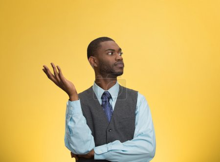 Photo pour Closeup portrait arrogant clueless young executive man, arm out asking why what problem so who cares, I don't know, isolated yellow color background. Negative human emotion facial expression feelings - image libre de droit