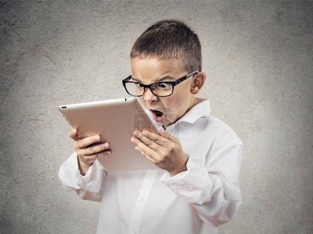 Shocked, frustrated boy using pad computer