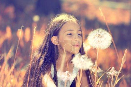 Photo pour Portrait en gros plan d'une belle et heureuse jeune fille soufflant des fleurs de pissenlit par une journée d'été ensoleillée. Vie Loisirs, vacances, concept de voyage. Expressions faciales positives, émotions, sentiments - image libre de droit