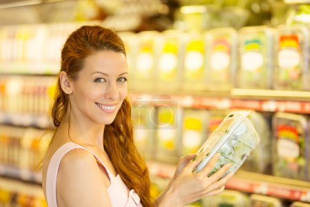 Happy woman shopping in a grocery store